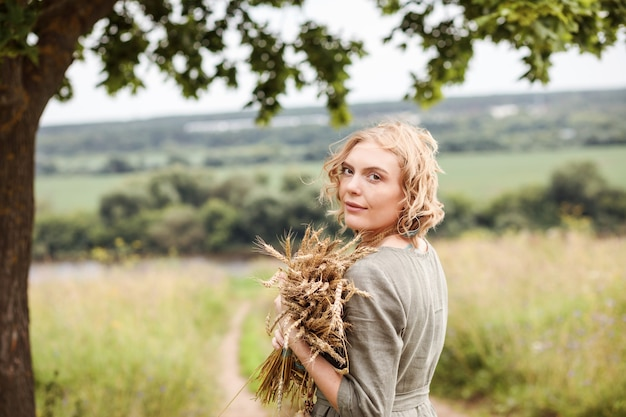 Porträt der blonden frau gekleidet in natürlichem leinenkleid mit weizenstrauß in ihren händen im sommer im freien.
