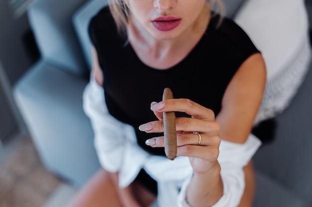 Porträt der blonden frau im körperanzug und im weißen hemd mit rosa schönen lippen, die zigarre halten