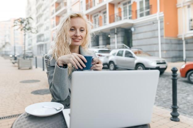 Porträt der blonden frau im straßencafé mit laptop-computer