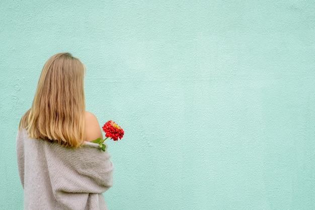 Porträt der blonden frau mit blume, die gegen blaue wand steht. rückansicht