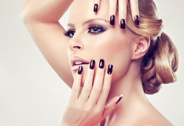 Porträt der blonden frau mit eleganter retro-frisur mit großem haarknoten. lange nägel an den fingern werden durch die schwarze farbe, das make-up im stil rauchiger augen auf ihrem gesicht gepflegt. glanz und eleganz.