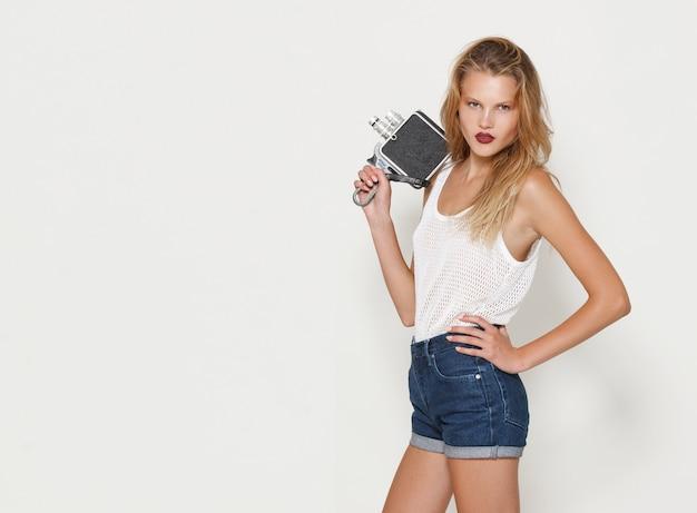 Porträt der blonden jungen frau, die in der weißen modekleidung posiert, wegschaut und eine retro-kamera in der hand hält. platz kopieren.