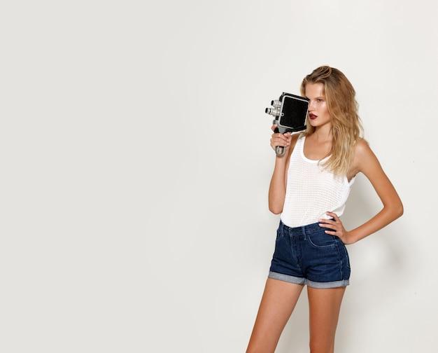 Porträt der blonden jungen frau, die in weißer modekleidung posiert, machen sie ein video mit einem retro-camcorder. platz für text.