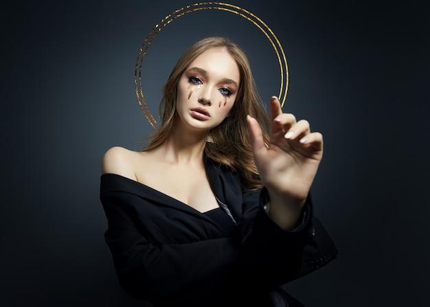 Porträt der blonden sexy frau mit dem langen haarhalo-nimbus über ihrem kopf auf schwarz