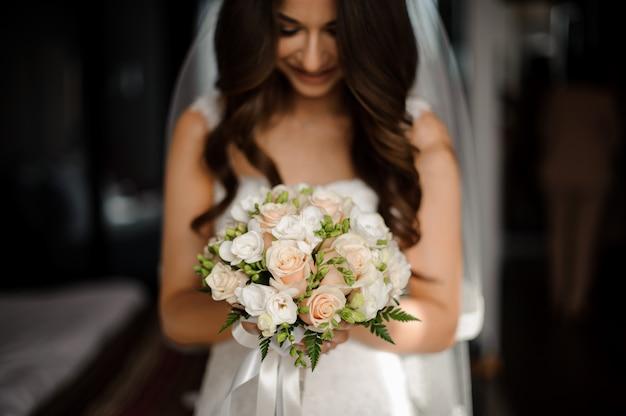 Porträt der braut im langen kleid und im stilvollen blumenstrauß mit rosen