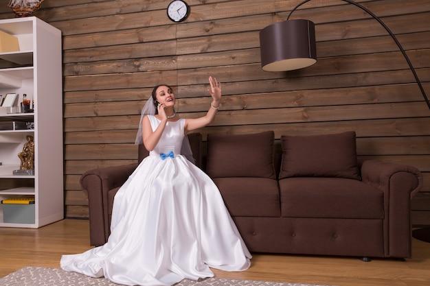 Porträt der braut im weißen kleid, das durch handy spricht und ehering auf ihrer hand betrachtet