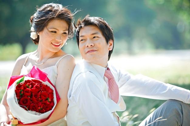 Porträt der braut und des bräutigams, die blickkontakt mit rosafarbenem blumenstrauß machen
