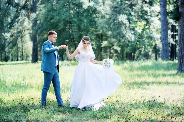Porträt der braut und des bräutigams mit einem blumenstrauß im park