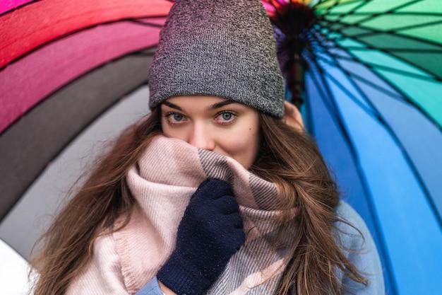 Porträt der brünetten frau mit großen schönen glücklichen augen, die in warmen schal und kuschelige kleidung mit hellem mehrfarbigem regenbogenschirm eingewickelt werden