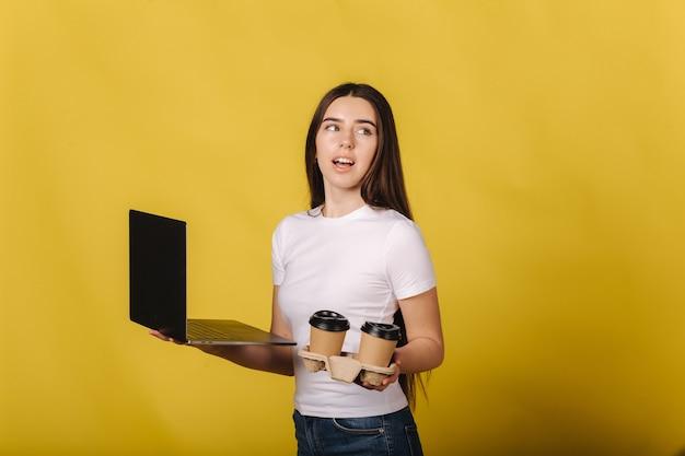 Porträt der brünetten frau mit laptop und halten zwei tasse cappuccino