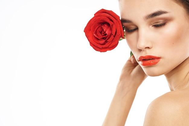 Porträt der brünetten frau mit rotem lippenstift und einer rose