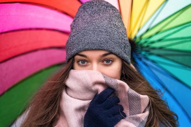 Porträt der brünetten frau mit schönen glücklichen augen, die in warmen schal und kuschelige kleidung mit hellem mehrfarbigem regenbogenschirm eingewickelt werden