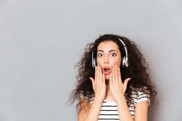 Porträt der brunettemischrassefrau, die musik über die drahtlosen kopfhörer setzen hände zum mundbedeutungsüberraschung über grauer wand hört