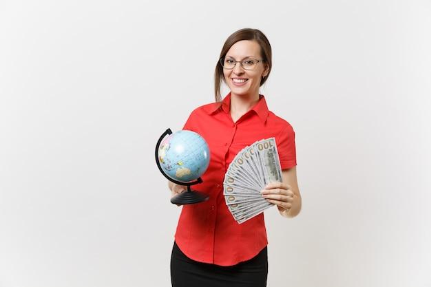 Porträt der business-lehrer-frau im roten hemd mit globus viele dollar, bargeld isoliert auf weißem hintergrund. bildungslehre an der high school universität, tourismus, auslandsstudium konzept.