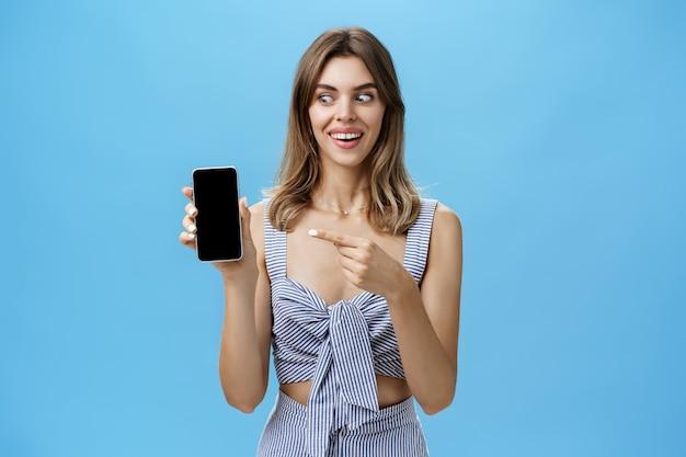 Porträt der charismatischen erstaunten und glücklichen frau mit niedlichen zahnlücken lächelnd axcited und überrascht halten fantastisches smartphone zeigt auf gerätebildschirm und schaut gadget erstaunt und entzückt