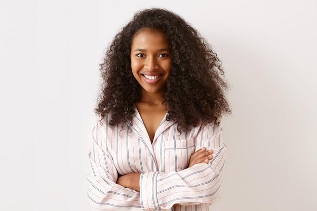 Porträt der charmanten attraktiven jungen afroamerikanischen frau mit voluminösem afro-haarschnitt mit breitem selbstbewusstem lächeln, die arme auf der brust verschränkt, gestreiftes nachthemd tragend