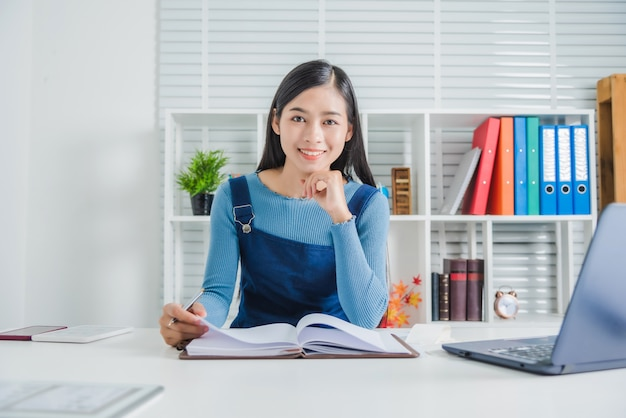 Porträt der charmanten dame des jungen weiblichen lächelns mit notizbuchpapier, attraktive asiatische frau, die glücklich fühlt.