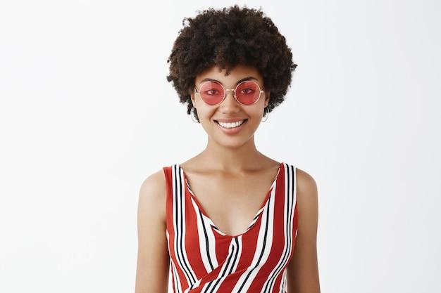 Porträt der charmanten sorglosen und niedlichen afroamerikanischen frau in der sonnenbrille und in den trendigen gestreiften kleidern, die freudig lächeln