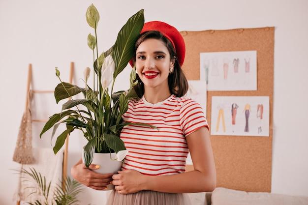 Porträt der dame im gestreiften hemd hält pflanze. hübsche frau im hellen t-shirt und in der roten baskenmütze, die vor der kamera mit blume in ihren händen aufwirft.