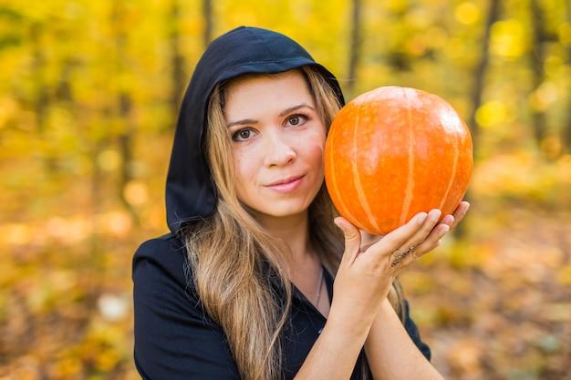 Porträt der dramatischen schönen blonden jungen frau, die kürbis im wald hält. halloween tag.