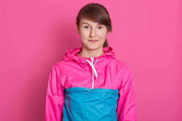 Porträt der eignungsfrau, die nach dem training im fitnessstudio aufwirft, blaue und rosa sportbekleidung trägt, direkt in die kamera schaut, dunkles haar hat