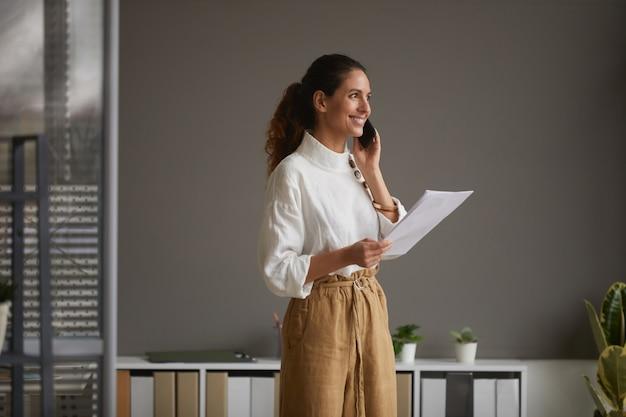 Porträt der eleganten erfolgreichen geschäftsfrau, die durch smartphone spricht und glücklich lächelt, während sie gegen graue wand im büro steht, raum kopieren