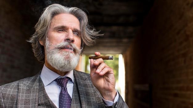 Porträt der eleganten männlichen rauchenden zigarre