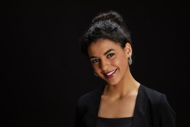 Porträt der eleganten nahöstlichen frau, die an der kamera lächelt, während sie gegen schwarzen hintergrund an der partei steht, kopieren raum