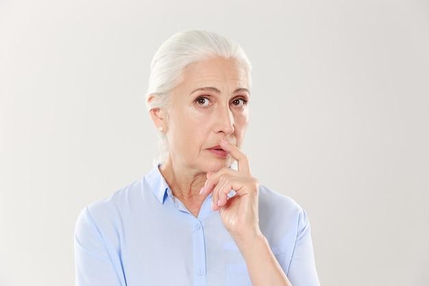 Porträt der eleganten reifen frau mit finger auf ihren lippen