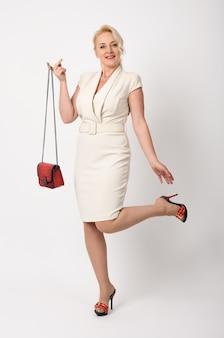 Porträt der eleganten schönen frau mit roter kleiner tasche