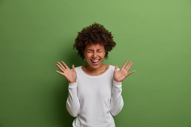 Porträt der emotional positiven dunkelhäutigen frau lacht laut, hat spaß drinnen, hebt die handflächen, hält die augen geschlossen, trägt einen weißen pullover, sieht sorglos und entspannt aus, isoliert an der grünen wand