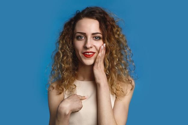 Porträt der emotionalen positiven jungen kaukasischen frau mit dem lockigen lockigen haar, das aufwirft, aufgeregten blick hat, glücklich lächelt, gesicht berührt und zeigefinger auf sich zeigt