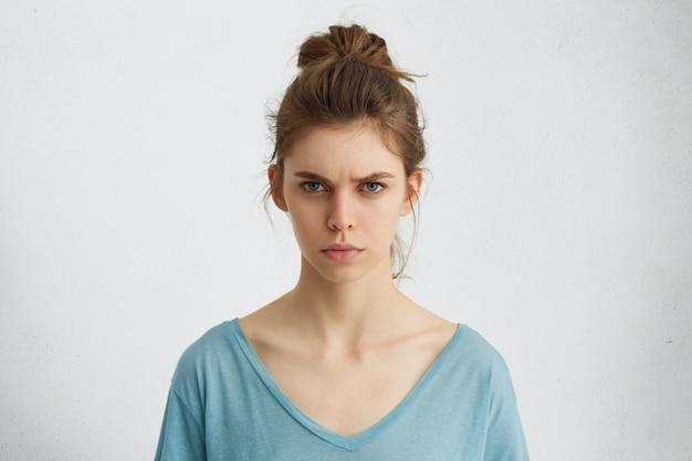 Porträt der empörten jungen frau mit ovalem gesicht, blauen augen und haarknoten, die blauen lässigen pullover tragen, der ihre augenbrauen runzelt und mit etwas unzufrieden ist.