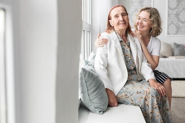 Porträt der enkelin und der großmutter, die zu hause auf fensterbrett sitzen