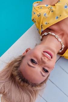 Porträt der entspannenden ruhigen frau im gelben sommerkleid liegt am rand des blauen schwimmbades, das die trendige muschelkette trägt