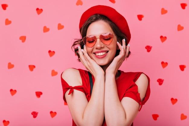 Porträt der entspannten attraktiven frau, die am valentinstag genießt. innenfoto des ansprechenden europäischen mädchens mit dunklem welligem haar.