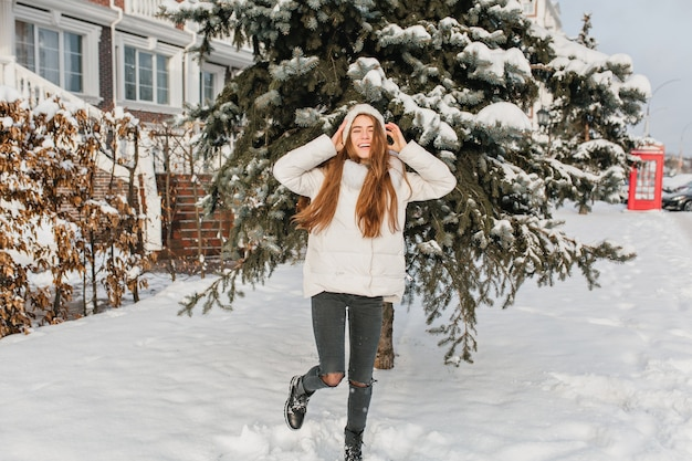 Porträt der entspannten blonden frau in der schwarzen hose, die an der verschneiten straße mit lächeln tanzt. foto im freien der lustigen anmutigen frau, die mit den händen oben vor der grünen fichte im wintertag aufwirft.