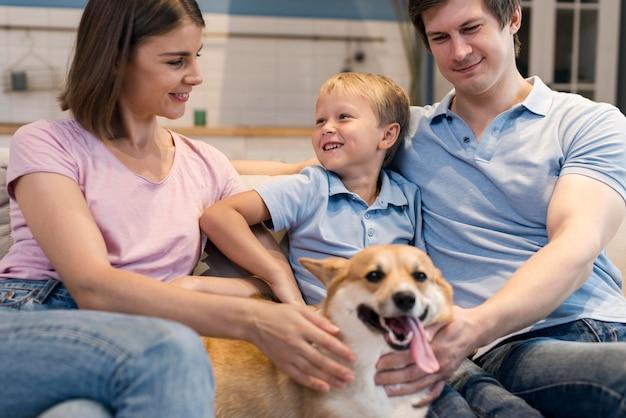 Porträt der entzückenden familie, die mit hund spielt