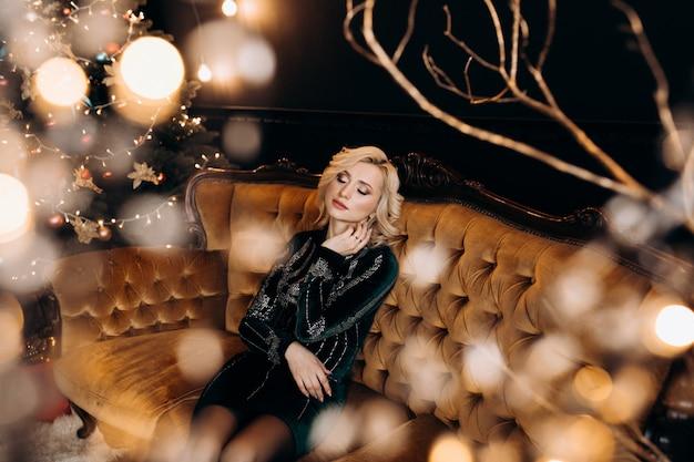 Porträt der entzückenden frau im schwarzen kleid, das in einer gemütlichen dunkelkammer mit weihnachtsdekor aufwirft