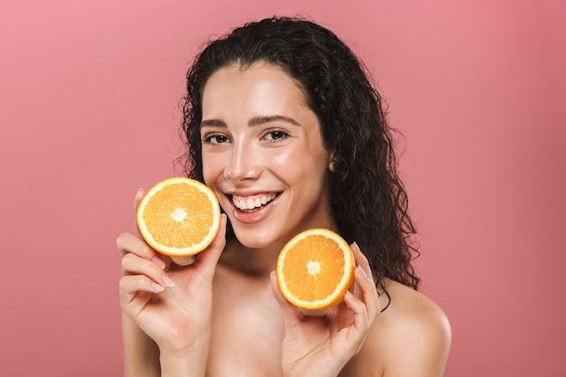 Porträt der entzückenden halbnackten frau mit dem langen haar, das lächelt und stücke von orange hält, lokalisiert über rosa hintergrund