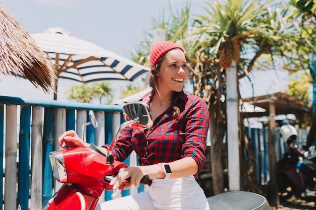 Porträt der entzückenden hübschen frau gekleidet im stilvollen outfit, das auf dem motorrad auf der insel reist. sommerreise, urlaub, aktiver lebensstil
