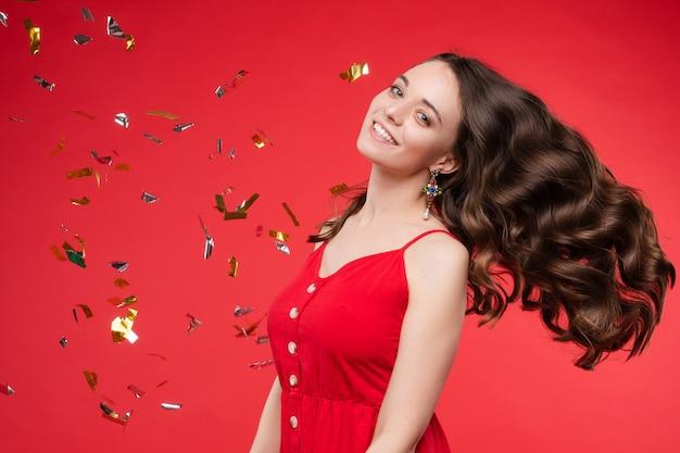 Porträt der entzückenden lächelnden jungen frau mit dem langen gelockten haar, das am roten studiohintergrund aufwirft