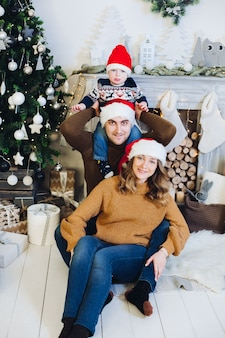 Porträt der entzückenden liebenden familie mit dem sohn auf den schultern des vaters, der vorne lächelnd am kamin und am weihnachtsbaum sitzt und alle weihnachtsmützen trägt