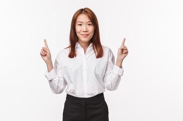 Porträt der erfolgreichen angenehmen asiatischen bürodame in hemd und rock, finger nach unten zeigend, hier klicken geste, lächelnd, zum auschecken promo einladen, produktwerbung auf weißer wand