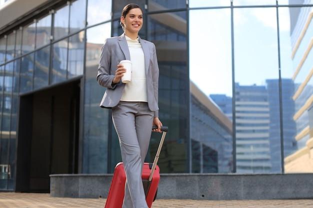 Porträt der erfolgreichen geschäftsfrau, die mit fall am flughafen reist. schöne stilvolle weibliche reise mit gepäck.