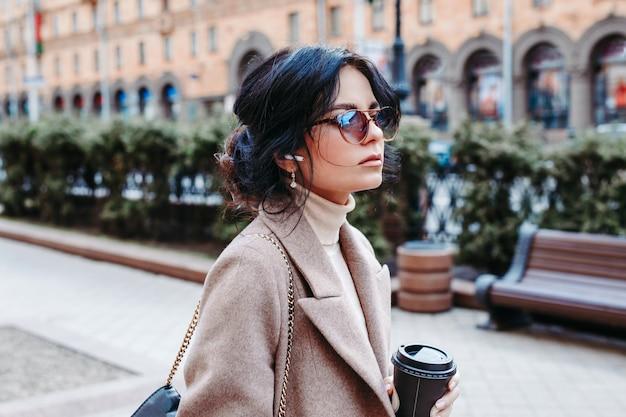 Porträt der erfolgreichen geschäftsfrau tasse kaffee auf ihrem weg zur arbeit in der hand halten