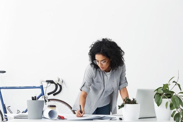 Porträt der erfolgreichen ingenieurin mit dunklem lockigem haar, das freizeithemd trägt