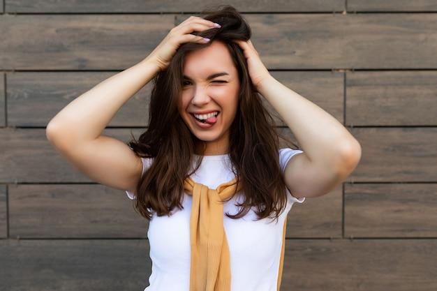 Porträt der erfolgreichen lächelnden freudigen glücklichen jungen brunetfrau, die lässiges weißes t-shirt und jeans trägt