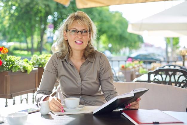 Porträt der erfolgreichen schönen blonden frau mittleren alters im sommerrestaurant im freien