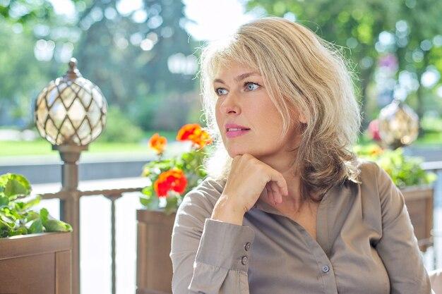 Porträt der erfolgreichen schönen reifen blonden frau im sommerrestaurant im freien, kopienraum